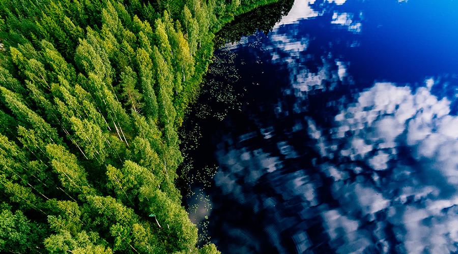 Ilmakuva, jossa näkyy kesäinen metsä ja järvi, johon pilvet heijastuvat.