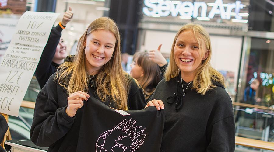 Kuvassa on kaksi hymyilevää tyttöä esittelemässä valmistamaansa tuotetta Nuori Yrittäjyys ry:n tapahtumassa.