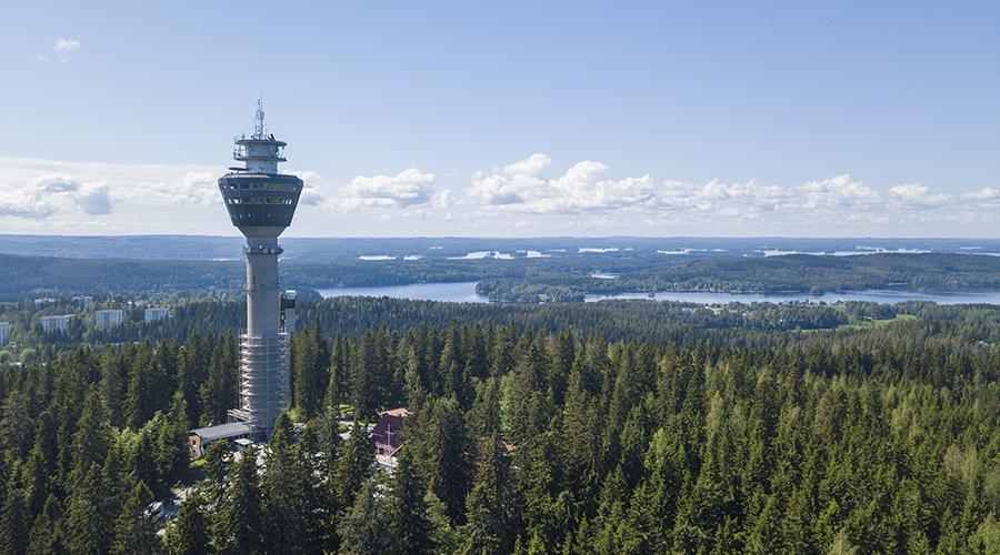 Kuvituskuva, jossa on Puijon näkötorni metsä- ja järvimaisemassa kesällä.