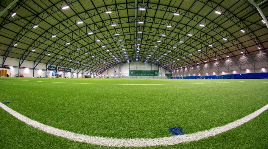 Kuvassa on sisäkuva Hämeenlinnan Säästöpankki Areenasta, jossa on vihreä tekonurmi ja runsaasti tilaa mm. jalkapallon pelaamiseen.
