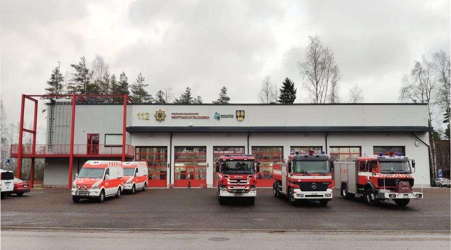 Kuvassa on Mäntyharjun pelastusasema, jonka eteen on pysäköity kolme paloautoa ja kaksi ambulanssia.