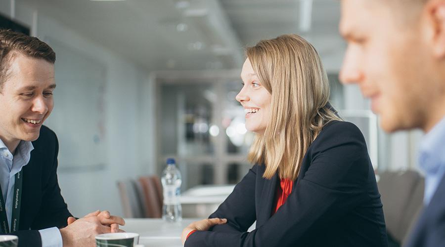 Kuvituskuva, jossa kolme henkilöä keskustelee iloisina toimistoympäristössä.