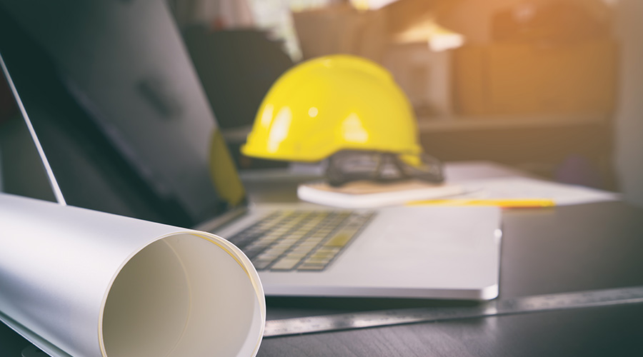 Kuvituskuva, jossa on tietokone, rullalle kääritty paperi sekä keltainen työmaakypärä.