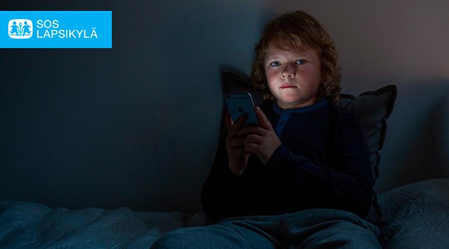 Kuvituskuva, jossa lapsi istuu pimeässä huoneessa ja käyttää kännykkää.