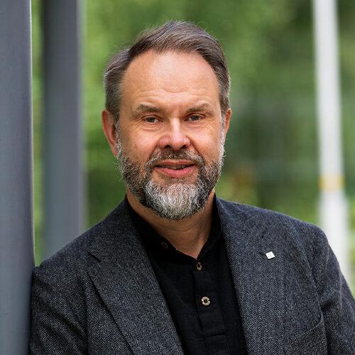 Tuusulan kuntakehitysjohtaja Heikki Lonka. Kuvassa harmaahiuksinen ja -partainen mies, joka nojaa pylvääseen. Taustalla vehreää kesäistä maisemaa.