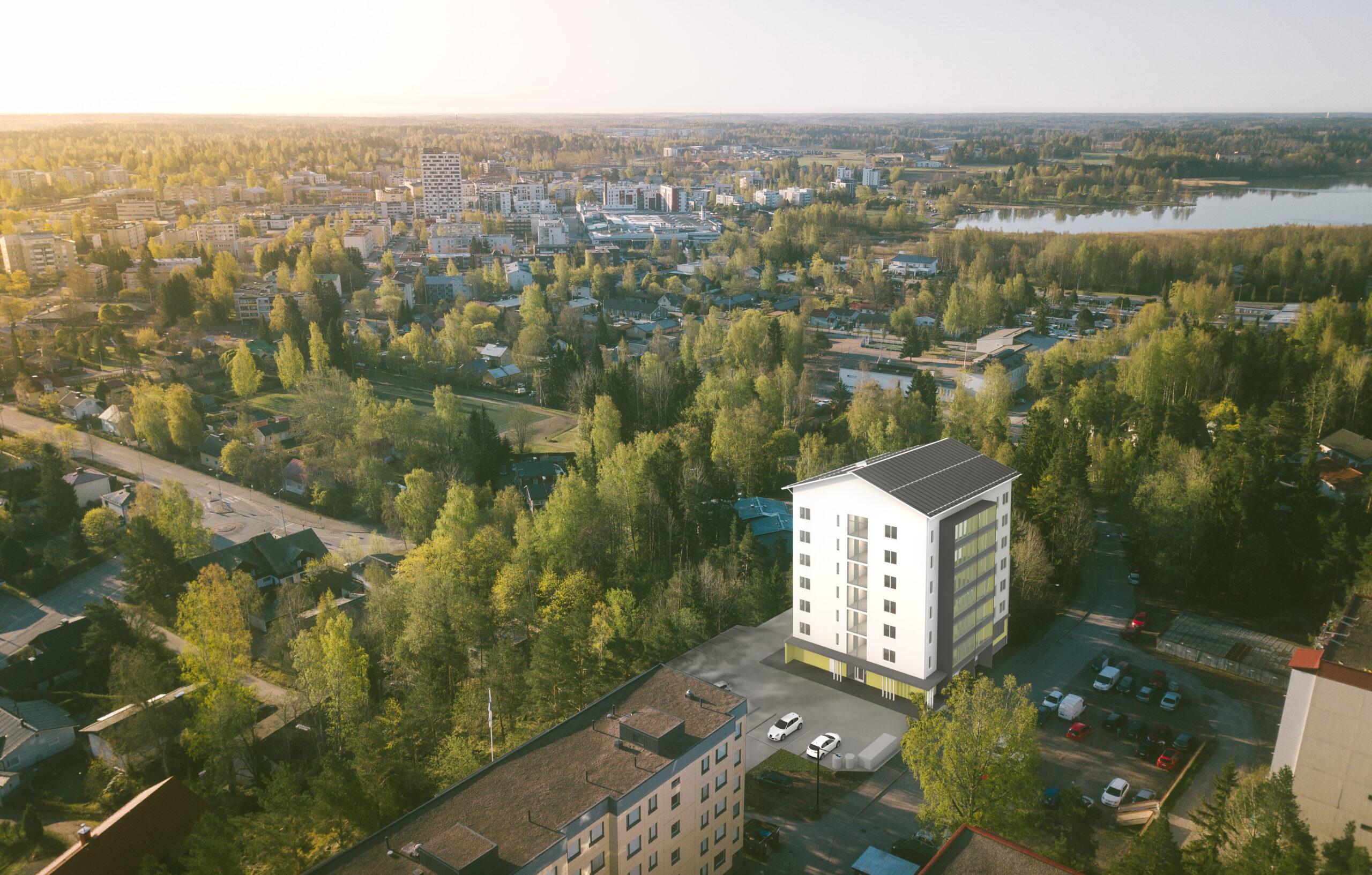 Havainnekuva, Järvenpään Mestariasunnot. Valkoinen kerrostalo Järvenpään keskustassa. Taustalla metsää, järvi ja kaupungin keskustaa.