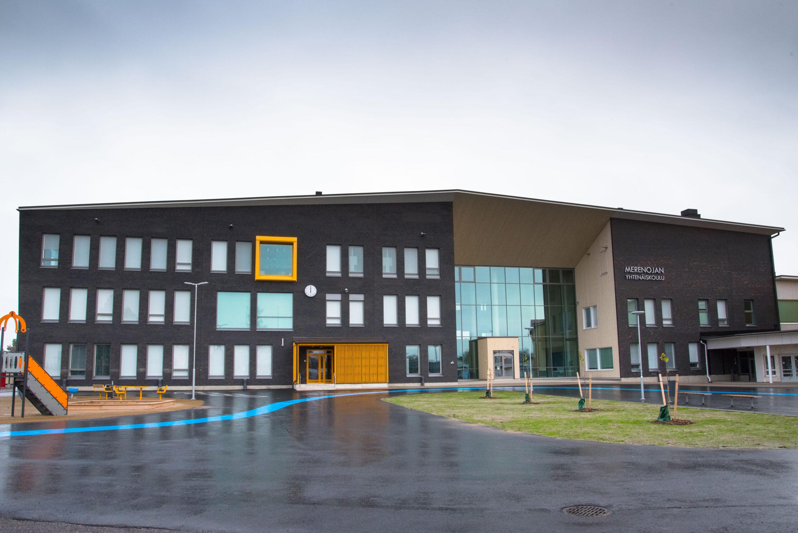 Kuvassa on suuri, moderni koulurakennus pihalta kuvattuna.