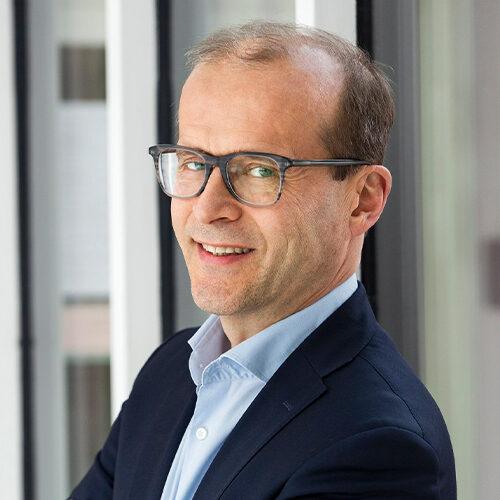 Tuusulan kunnan talousjohtaja Markku Vehmas. Kuvassa vaalealla taustalla silmälasipäinen mies, joka nojaa lasiseinään.