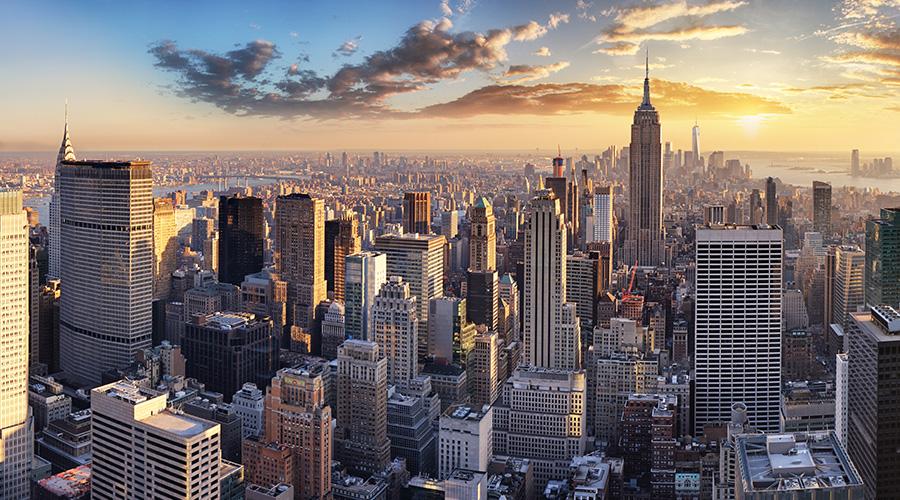Kuvituskuva, jossa aurinko nousee New Yorkissa pilvenpiirtäjien takana.