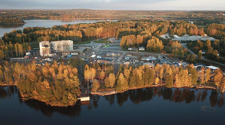Ilmakuva Lohjan Vuokra-asunnot Oy Lovan uudesta Sahapiha-talosta. Kuvassa modernin ja vaalean, kuusikerroksisen kerrostalon työmaa, jota ympäröi ruskainen järvimaisema.