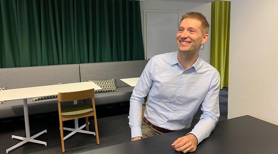 Kuva digitaalisten palveluiden asiantuntija Okko Rostedtista istumassa ja nauramassa pöydän ääressä