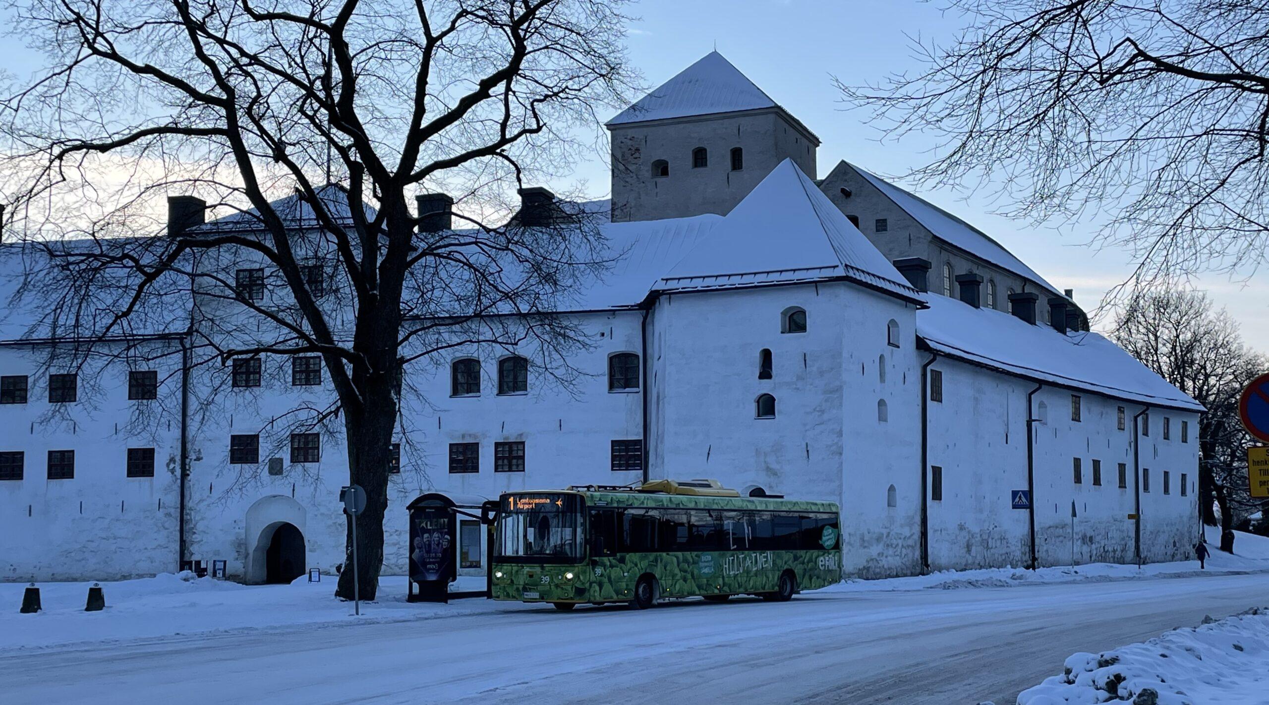 Kuvassa Turun Kaupunkiliikenteen sähköbussi talvisissa maisemissa Turussa.
