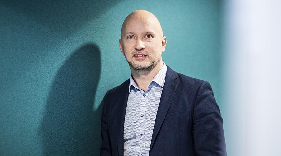 Hymyilevä mies (Rami Erkkilä) vihreän seinän vieressä kuvattuna.