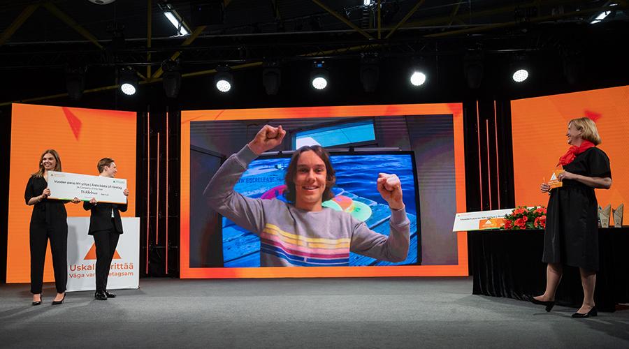 Nuori tuulettaa Uskalla Yrittää- tapahtuman lavan virtuaalinäytöllä