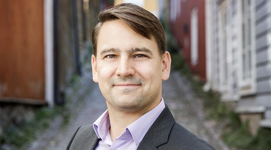 Porvoon kaupungin rahoitusjohtaja Henrik Rainio. Taustalla Porvoon vanhan kaupungin kapea, puutalojen reunustama mukulakivikatu.