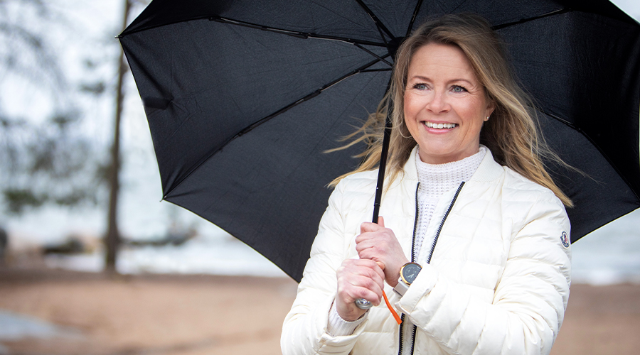 Kuntarahoituksen leasing-asiantuntija Krista Peltomäki. Vaaleahiuksinen, hymyilevä nainen valkoisessa kevyttoppatakissa kantaa mustaa sateenvarjoa.
