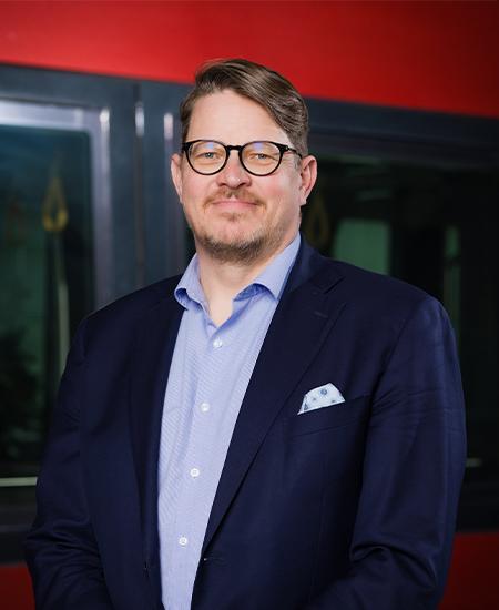 Tampereen Raitiotie Oy:n toimitusjohtaja Pekka Sirviö. Hymyilevä, silmälasipäinen mies pikkutakissa kuvattuna Tampereen Ratikan punaista kylkeä vasten.