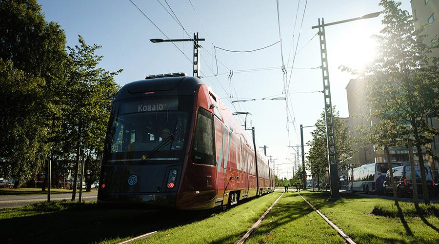 Tampereen Ratikan protovaunun koeajo Sammonkadulla syyskuussa. Punainen katujuna nurmipäällysteisillä kiskoilla aurinkoisessa syysmaisemassa.