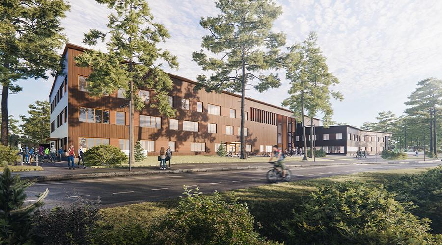Havainnekuva Valkealan monitoimitalosta Kouvolassa: kolmikerroksinen, mäntyjen reunustama, puuverhoiltu rakennus.