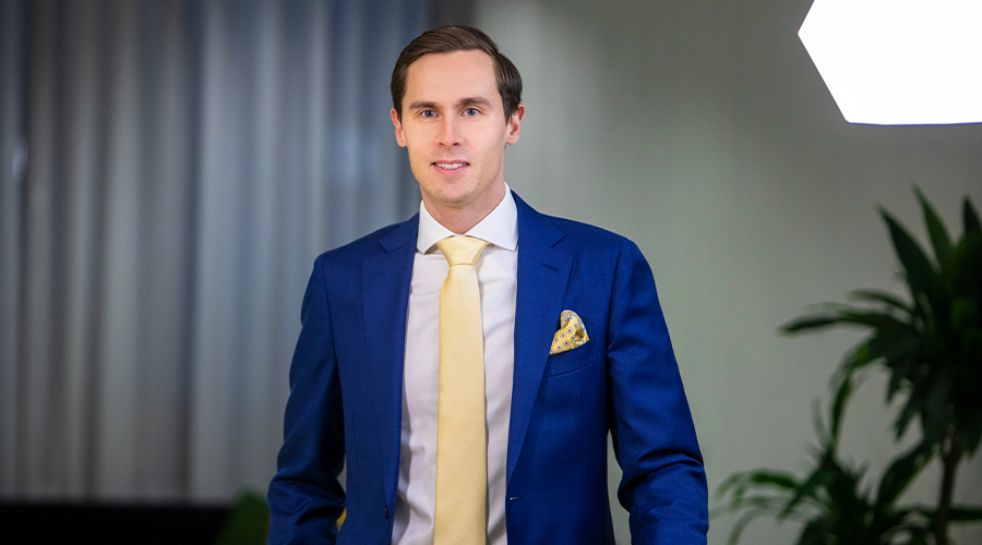 Kuntarahoituksen asiakkuuspäällikkö Mika Korhonen tummansinisessä puvussa ja haalean keltaisessa solmiossa.