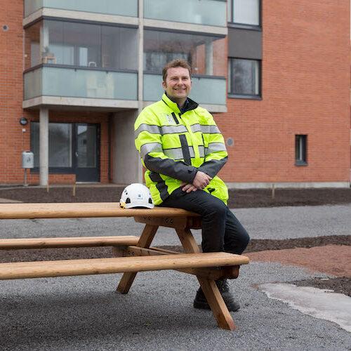 TVT Asuntojen kehittämispäällikkö Johannes Malmi istuu kerrostalon edessä heijastintakki päällään.