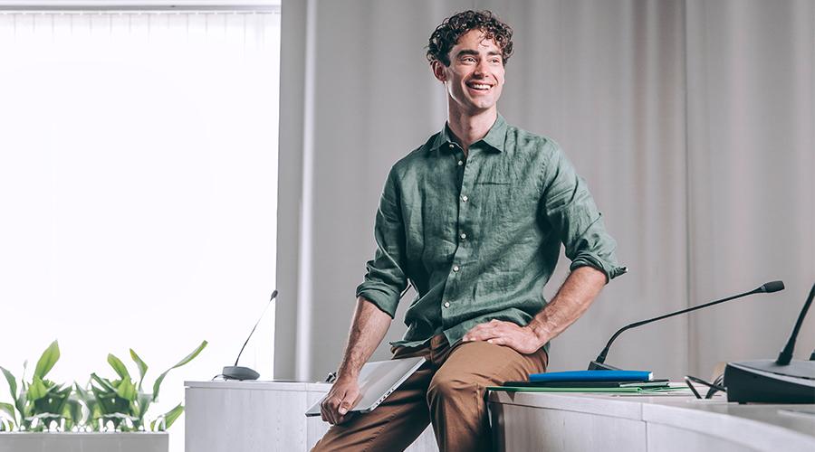 Kuvassa nuori mies istuu pöydän reunallä kädessään toetokone.