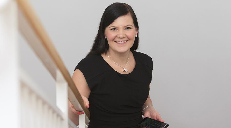 Laukaan kunnanjohtaja Linda Leinonen katsoo kameraan hymyillen vaaleasävyisessä rappukäytävässä. Kuva: Sanna Laitinen.