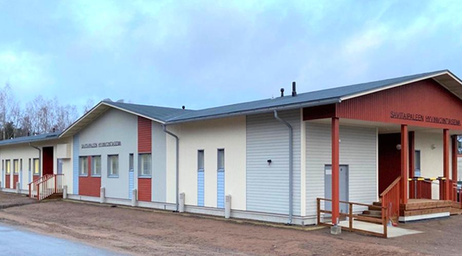 Savitaipaleen hyvinvointiasema rakennuksen valmistumisvaiheessa. Yksikerroksinen, harjakattoinen rakennus, jonka puuvuoraus lainaa punaisen, sinisen ja valkoisen sävyjä vanhan hyvinvointiaseman ulkokuoresta.