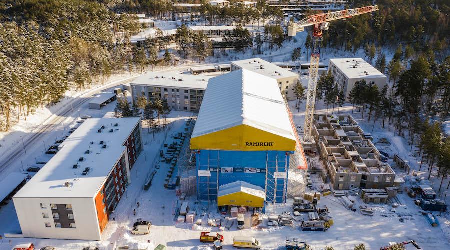 Kuvassa TVT Asuntojen rakennustyömaa lumisissa maisemissa puiden ympäröimänä.