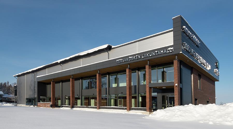 Tervakosken liikuntahallin teräksinen, punatiilinen ja lasinen julkisivu aurinkoisena talvipäivänä kuvattuna.