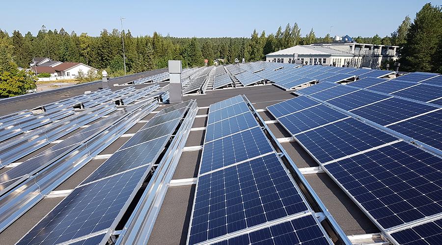 Aurinkopaneleeja rakennuksen katolla Vihdissä. Taustalla metsää ja taivasta.