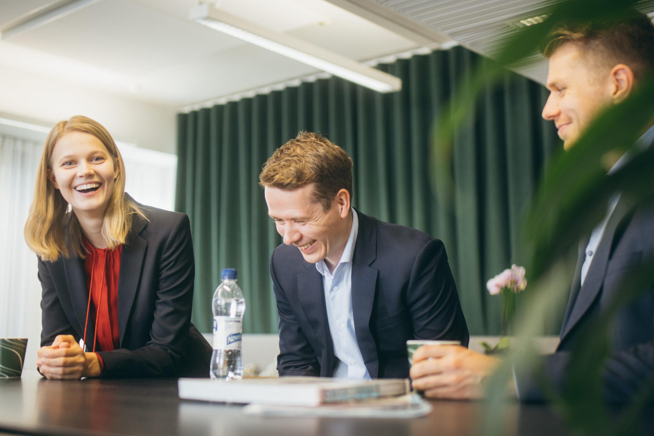 Kuvituskuva, jossa ryhmä iloisia ihmisiä istuu neuvotteluhuoneessa saman pöydän ääressä.