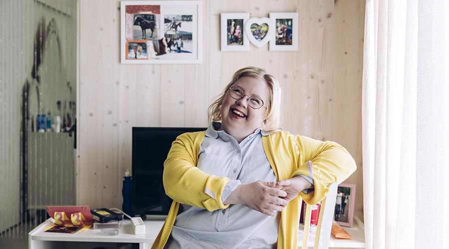 Iloinen vaaleahiuksinen Annika istumassa viihtyisässä kodissaan.