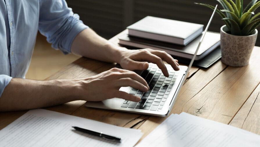 Kuvituskuva, jossa näkyvät henkilön kädet käyttämässä kannettavaa tietokonetta.