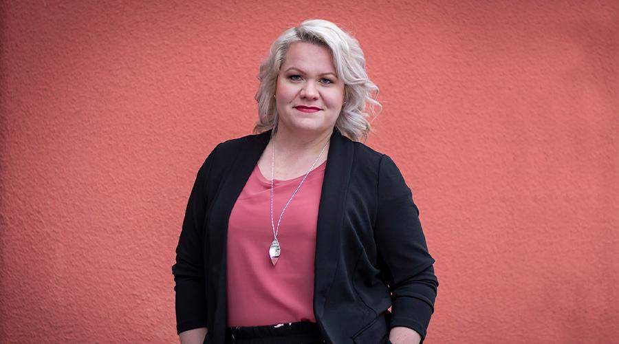 Närpiön kaupungin henkilöstöpäällikkö Marjo Österdahl kuvattuna punaista seinää vasten.