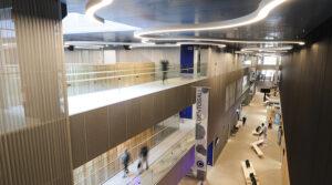 Sairaala Novan käytäviä ja puista seinää. Katossa kaarevia valoja